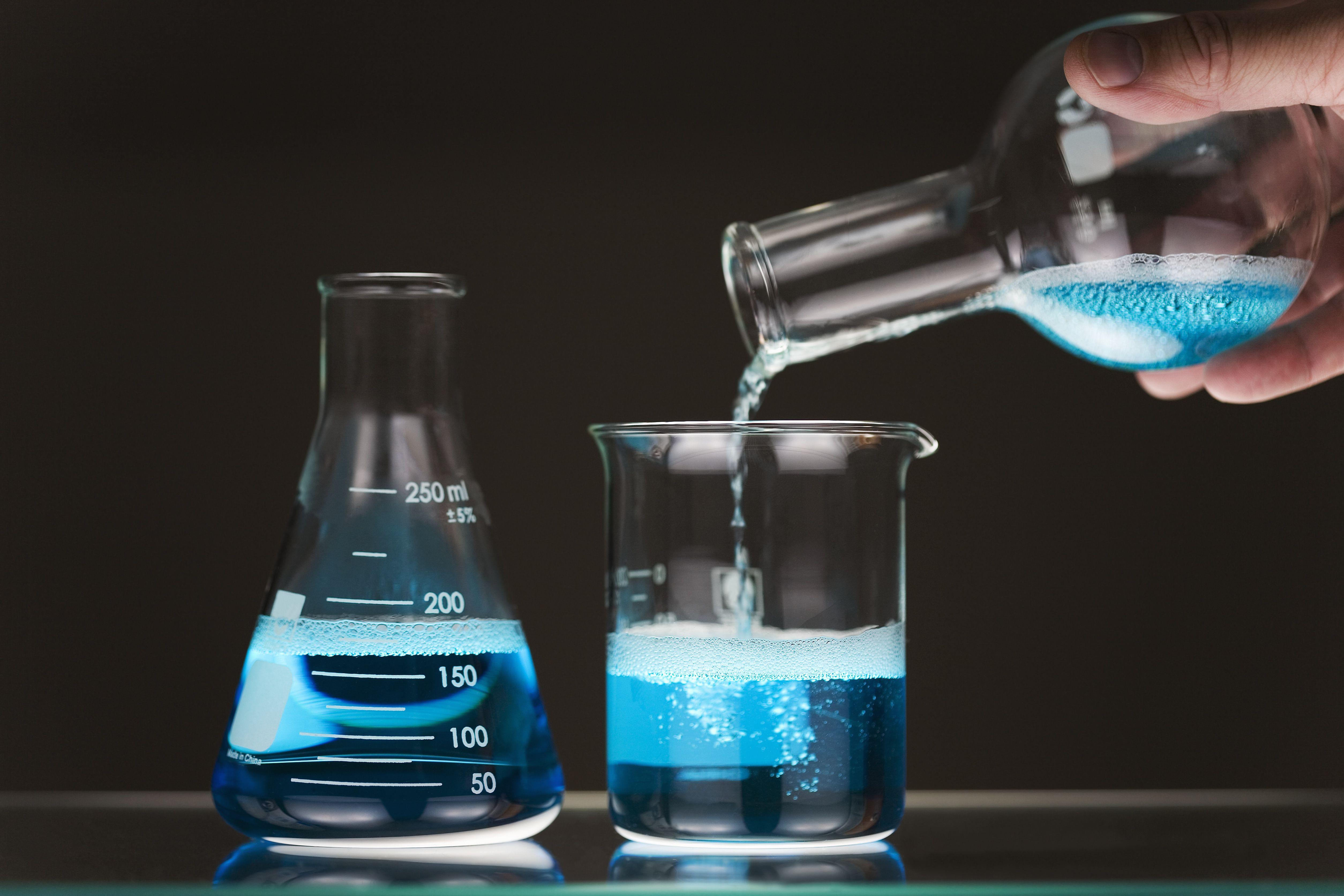 Pouring blue liquid between flasks