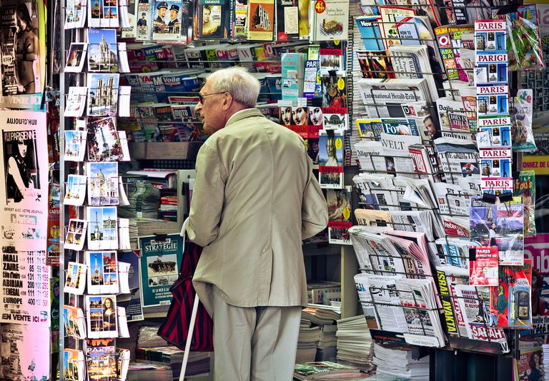 A man peruses a Parisian news stand