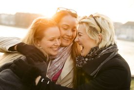 Three women friends laughing together outside.