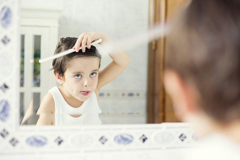 little boy combing hair in the mirror