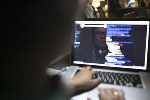 Reflection of female hacker coding working hackathon at laptop