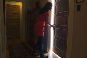 woman opening door to a lit room