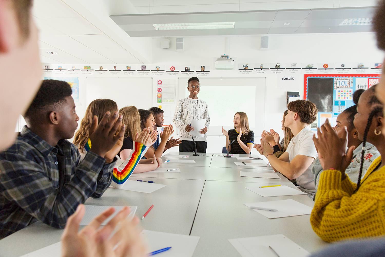 Schüler klatschen für Klassenkameraden in der Debattenklasse