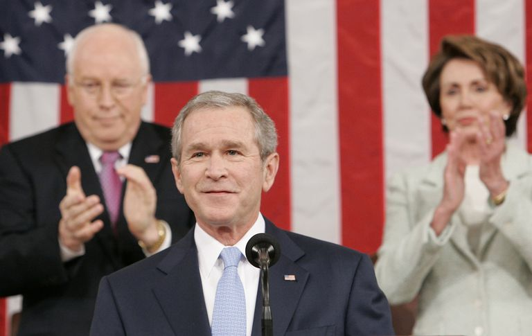 George W. Bush standing in front of flag and advisors smiling