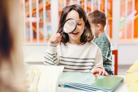 Girl smiling reading book with magnifying glass
