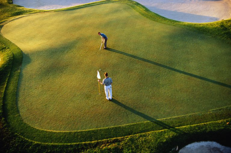 Golfer putting on green, man holding flag, aerial view