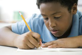 fifth grade male student uses a pencil to write in a notebook