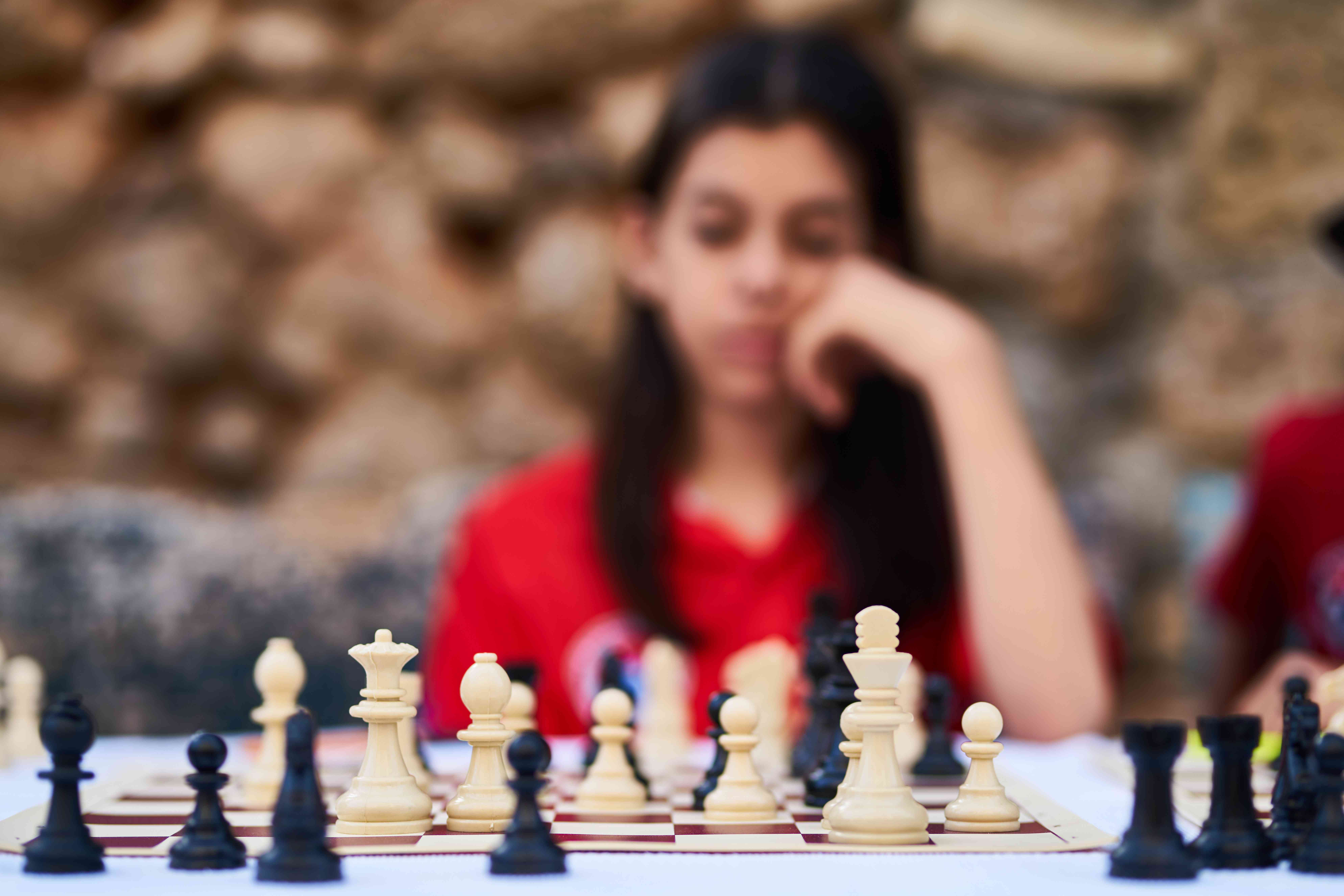 Chessboard with woman playing blurred in background.