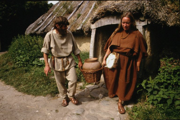 People dressed in Medieval peasant clothing carry a jug
