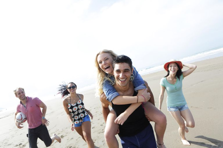 Young adults running on beach, couple piggyback