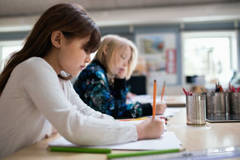 Side view of students writing on paper at desk in classroom