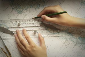 Woman's hands measuring on navigational chart.