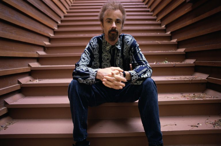 man with moustache and goatee, hands folded on knees, sitting on wide stairway