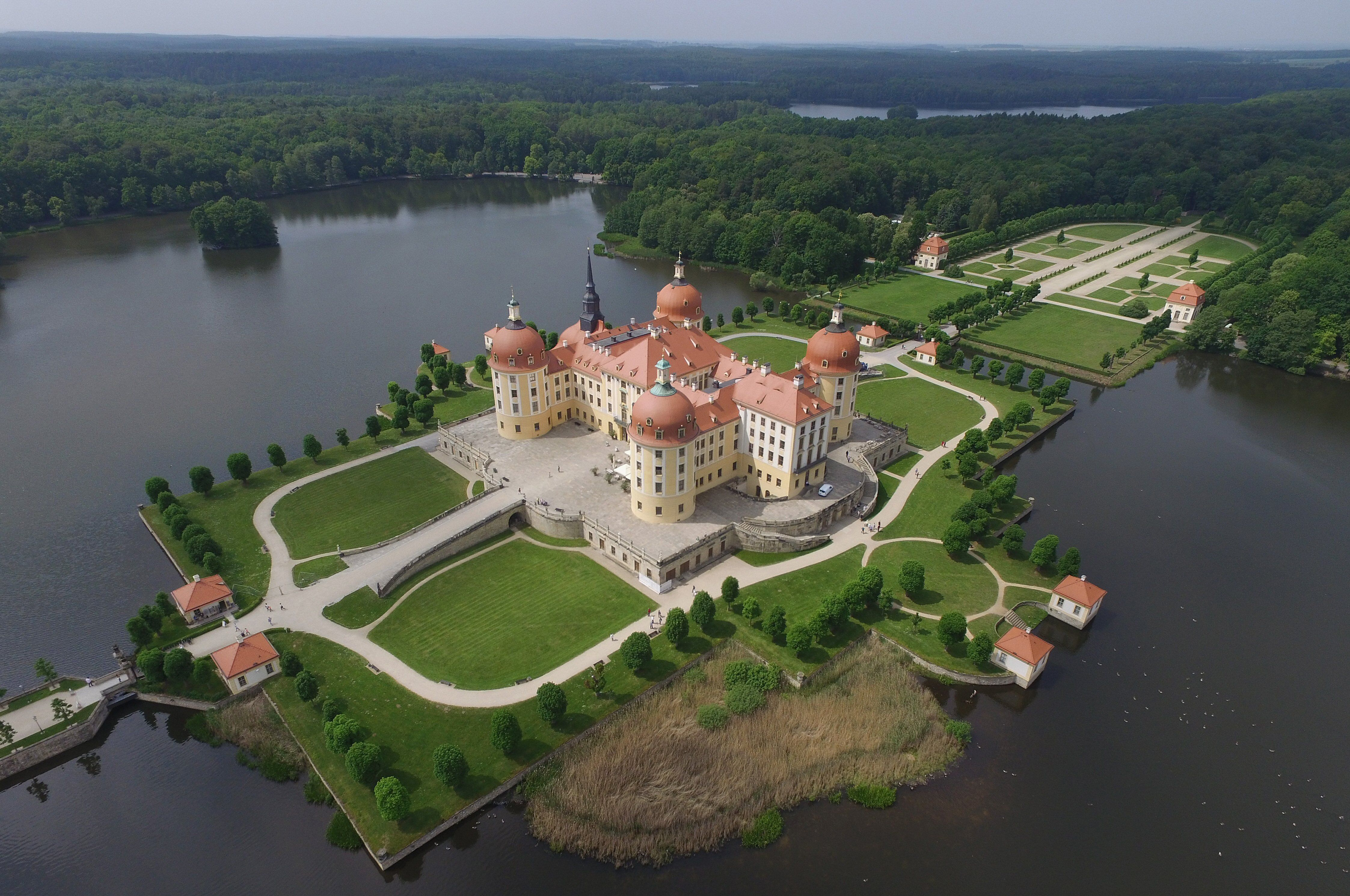 Overhead view of Moritzburg Castle, 4 red-domed turrets dominate the red hipped roof of this renovated hunting lodge nearly surrounded by water
