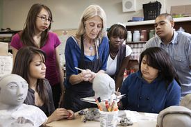 Teacher demonstrating sculpting to students.