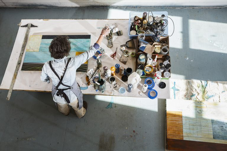 Overhead view of woman artist working on a painting in her bright, sunlit studio