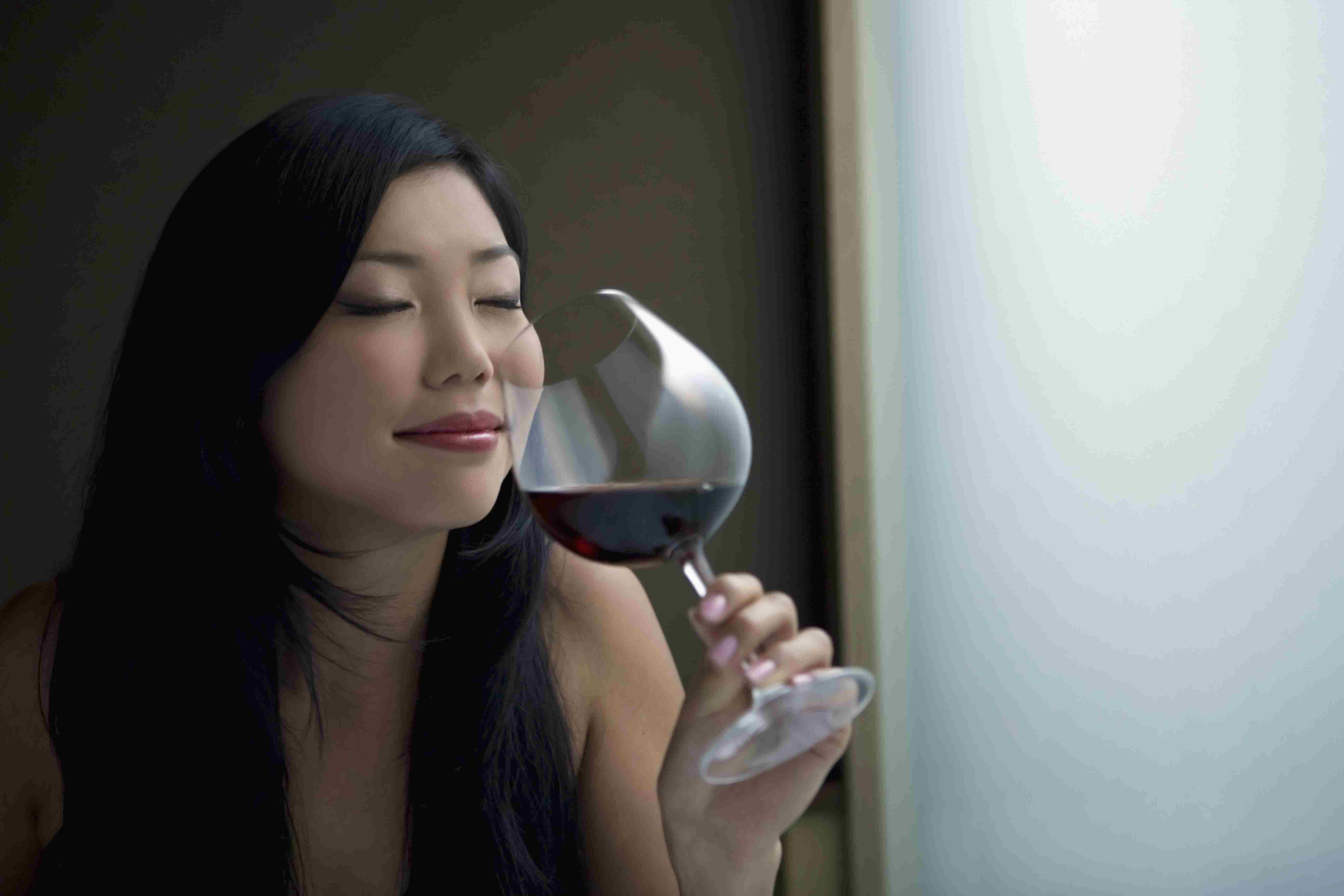 A woman smells red wine in a glass