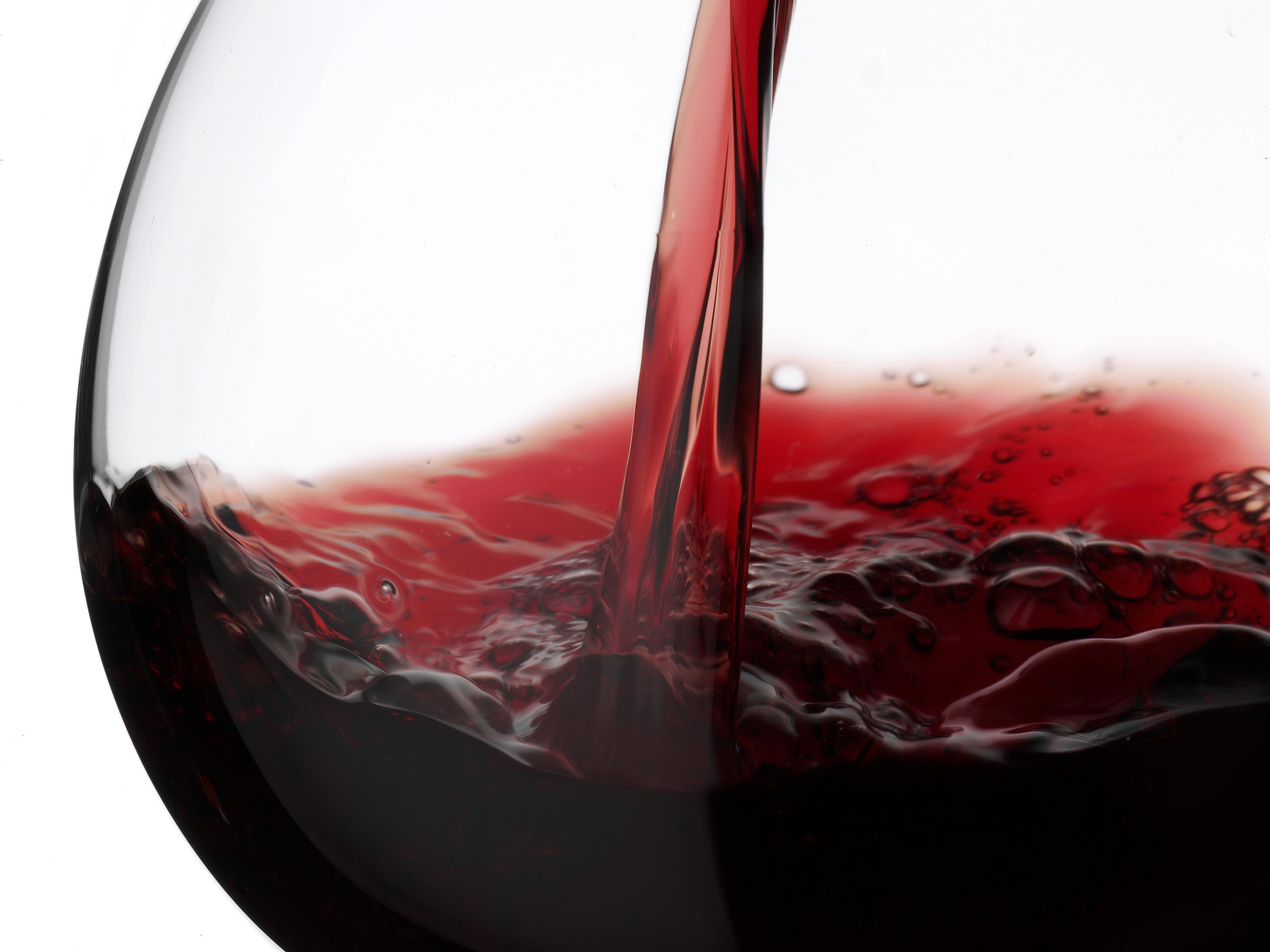 Wine being poured into a glass on a white background.