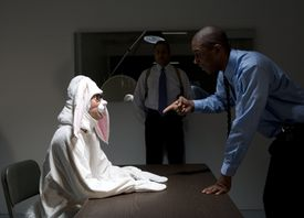 Person in rabbit suit being interrogated by police