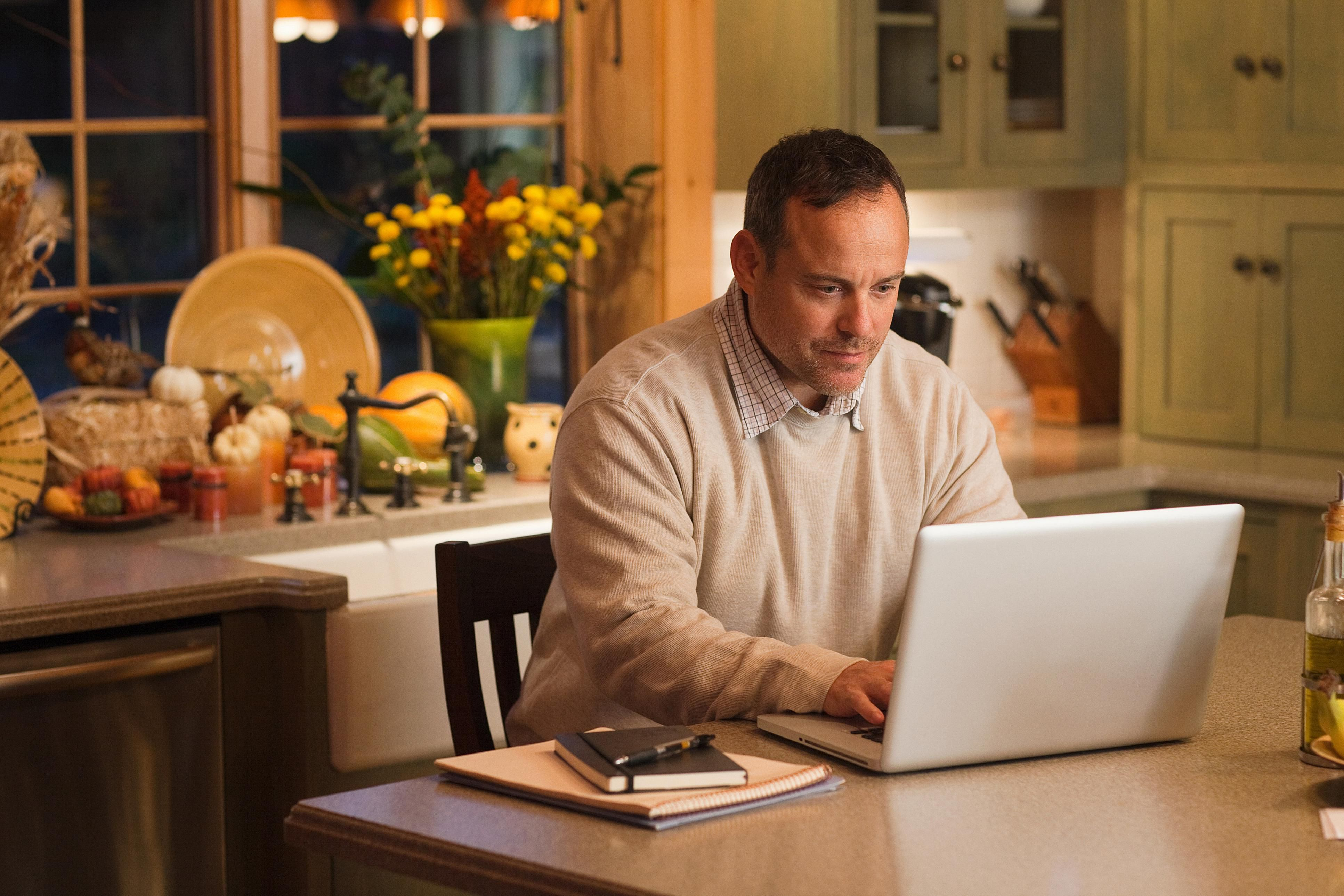 A man working on his laptop in his kitchen office