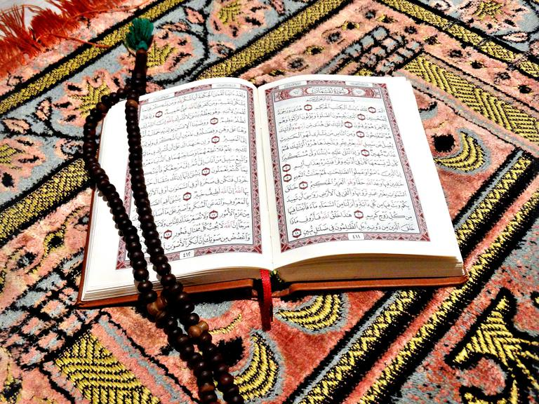 High Angle View Of Prayer Beads On Koran