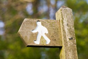 Wooden footpath directional sign showing carving of walking person