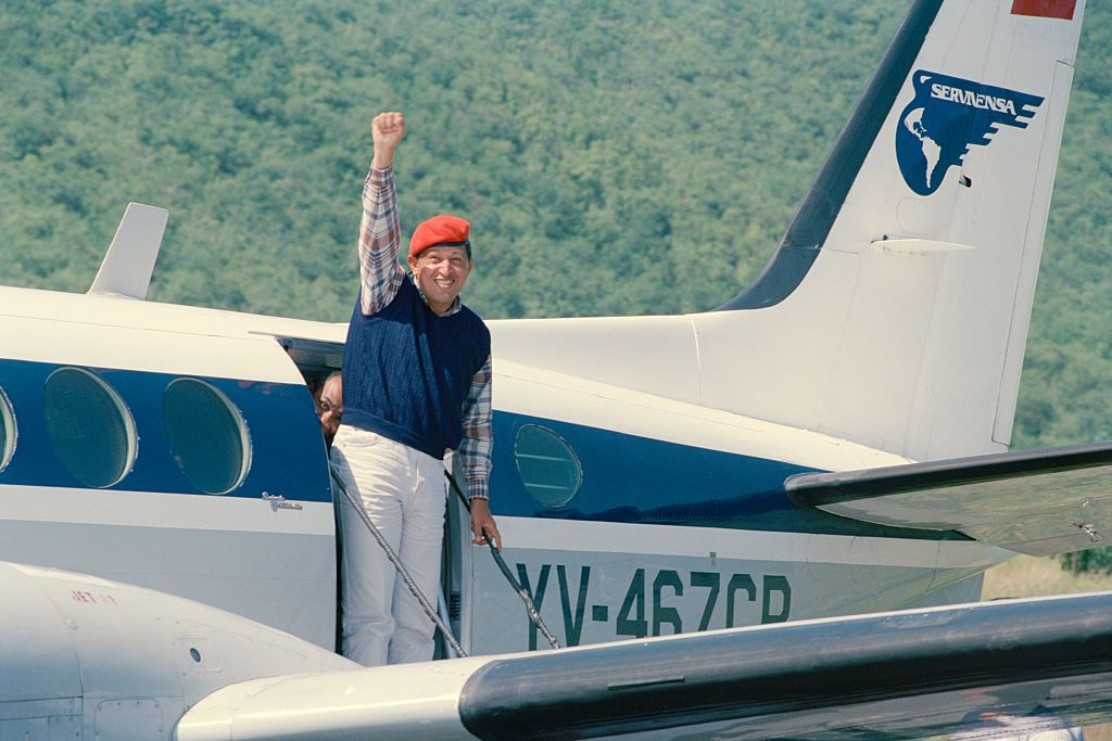 Hugo Chaves during campaign raising a fist getting off of a plane