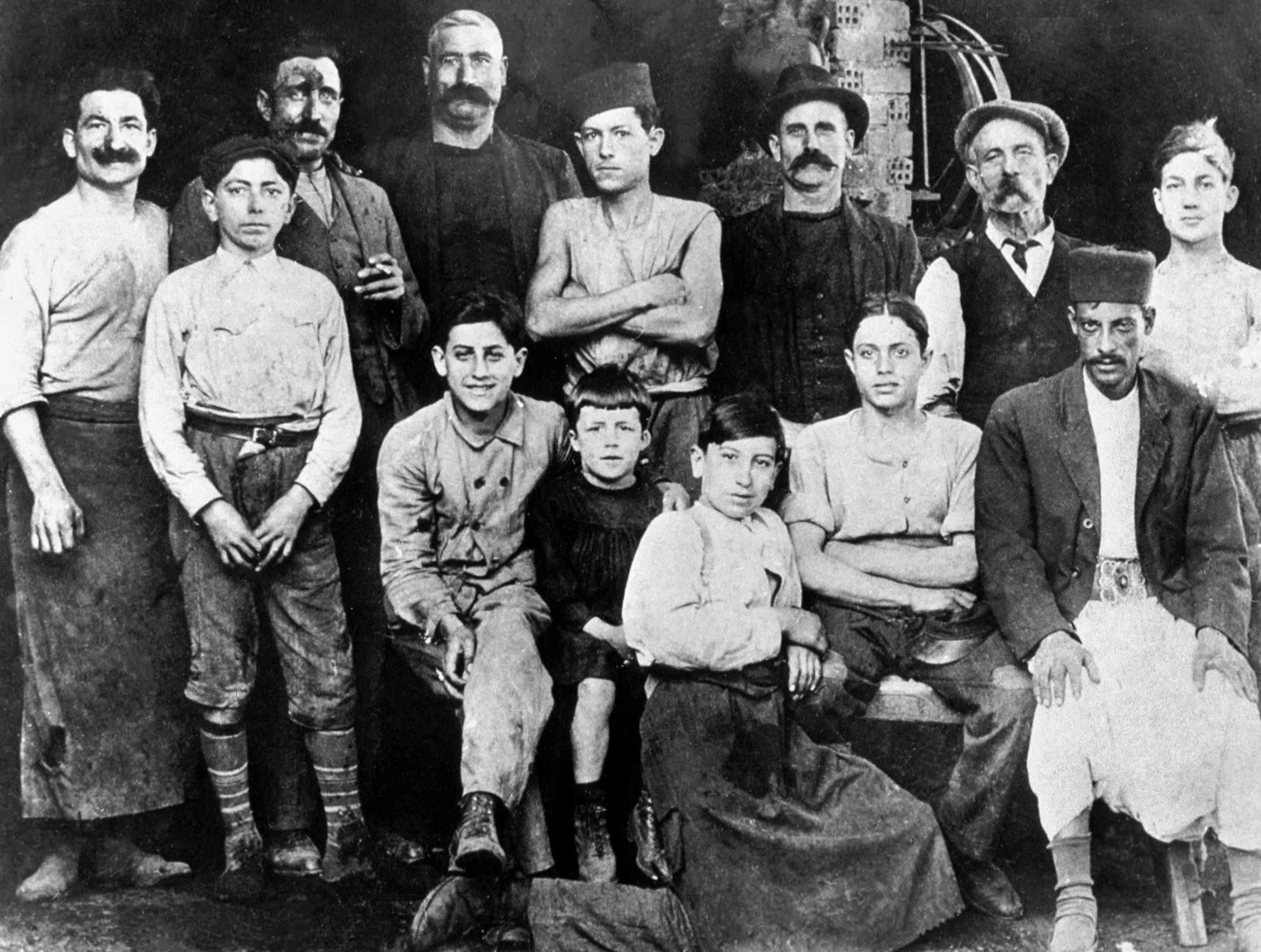 En el taller del tío de Camus (Etienne, Cooper) en Argel en 1920: Albert Camus (7 años) está en la c con traje negro