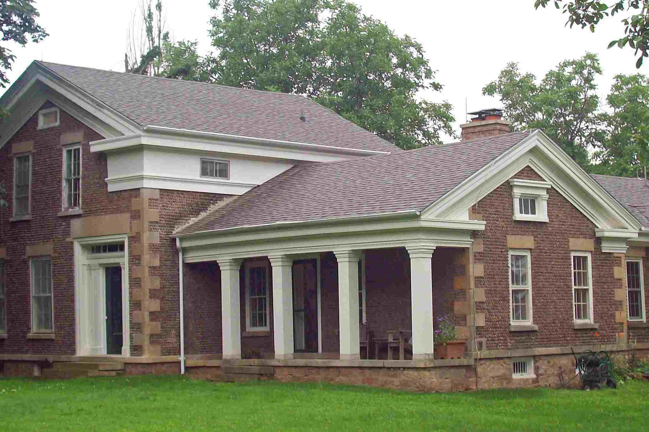 2 story front gable house with quoins and one-story side gable extension with open porch of 4 pillars