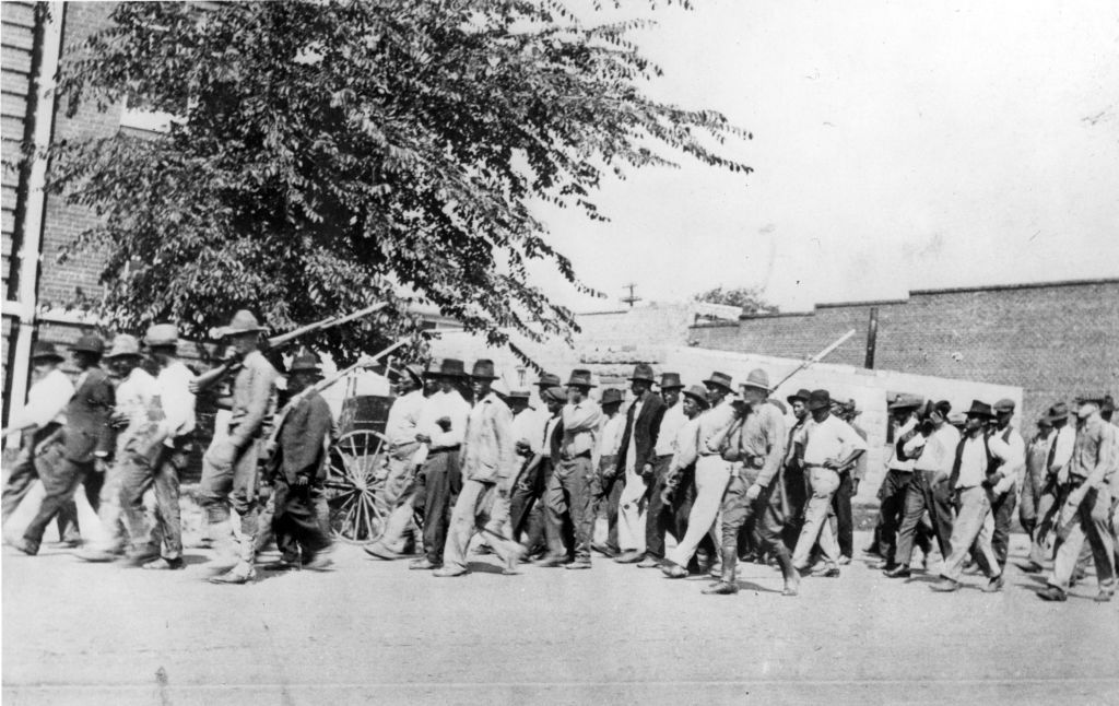A group of National Guard troops, carrying rifles with bayonets attached, escort unarmed Black men to a detention center after the Tulsa Race Massacre, Tulsa, Oklahoma, June 1921.
