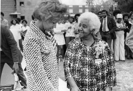 American inventor Marjorie Stewart Joyner (right) speaks with an unidentified woman at an outdoor event, late 1960s,black and white photograph.