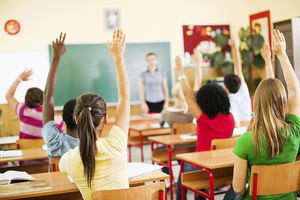 Group of students sitting in classroom with raised hands