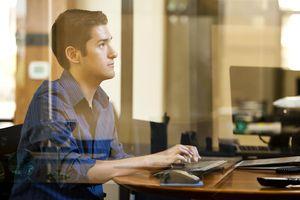 Man using a computer behind glass