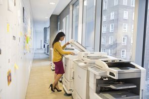 A woman using a printer and photocopier bank