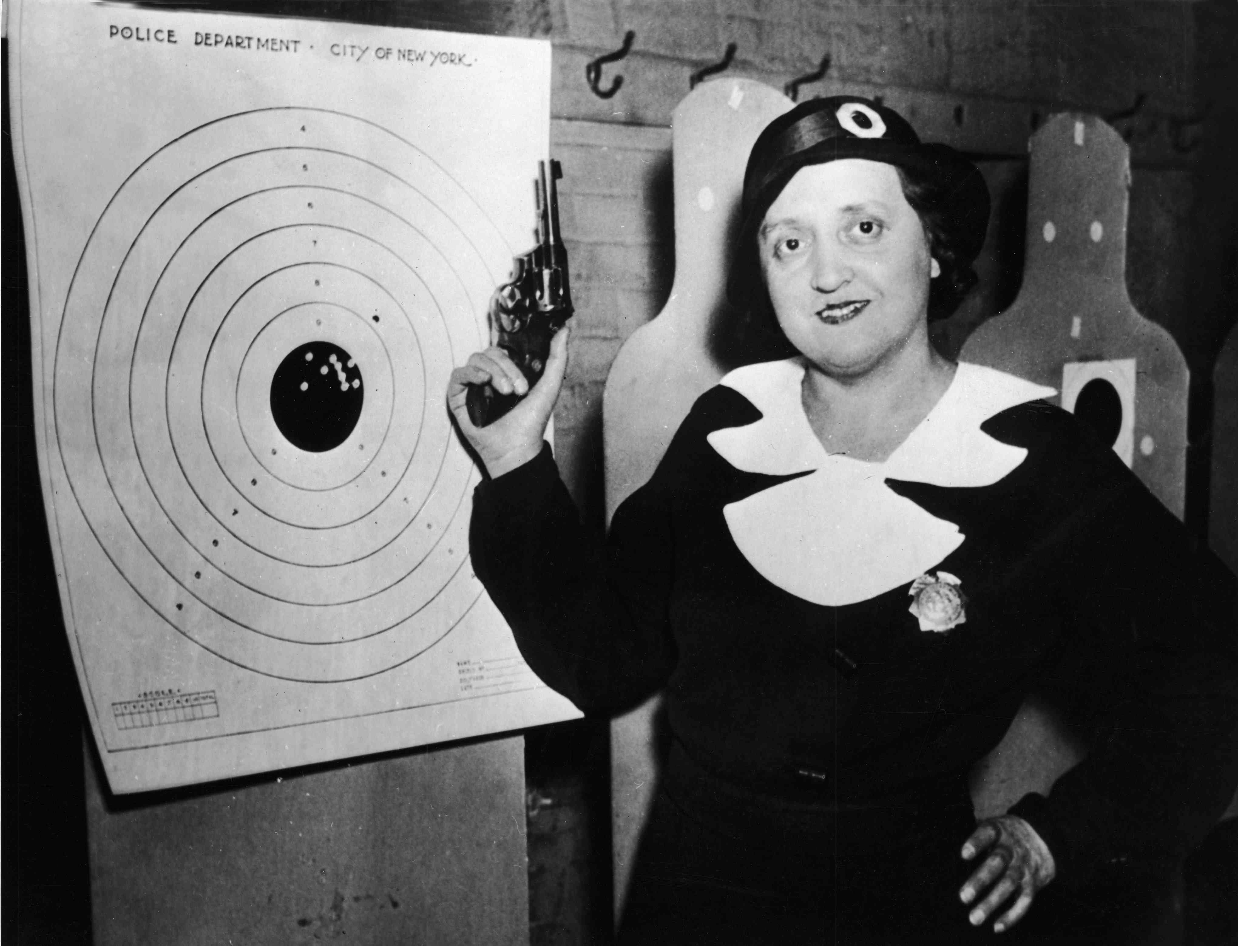 One of New York's then 105 policewomen stands with her gun and her target at the police firing range, New York, December 12, 1934.