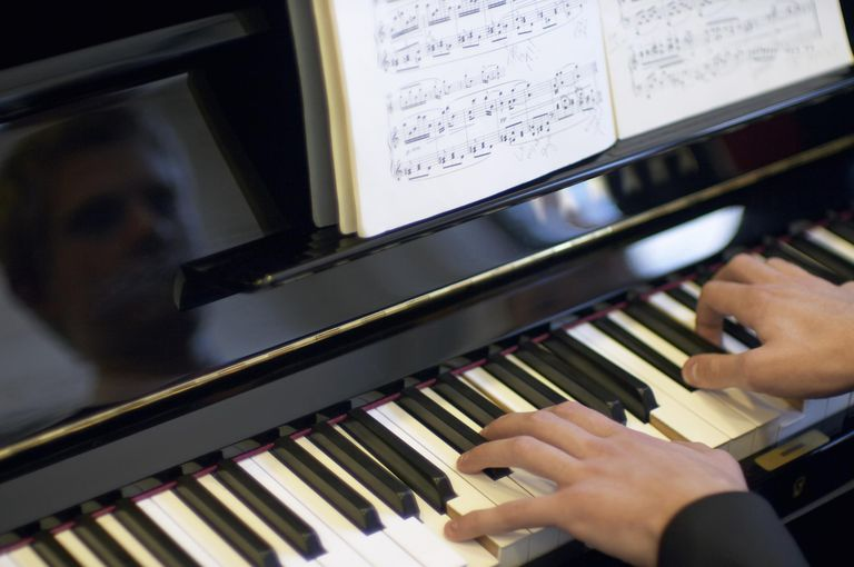 Man playing piano, close up of hands