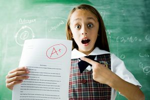 Schoolgirl hods up graded paper showing an A+