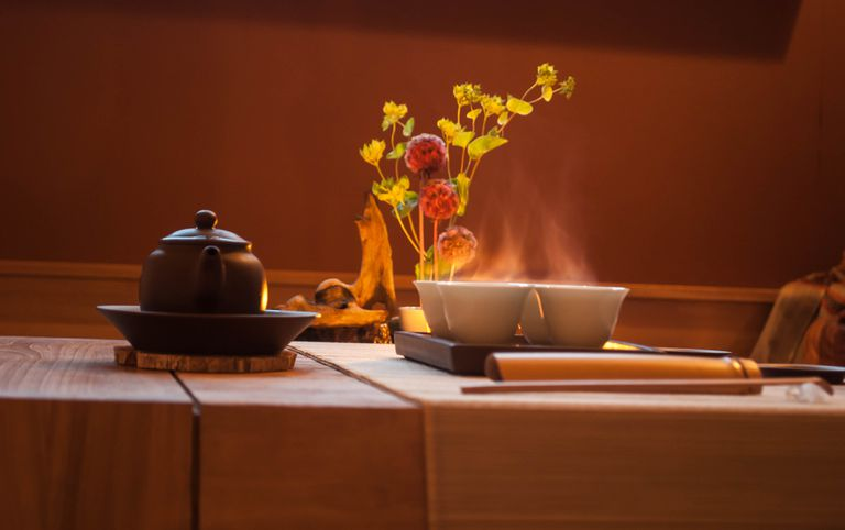 A chabana flower arrangement with a teapot and tea cups