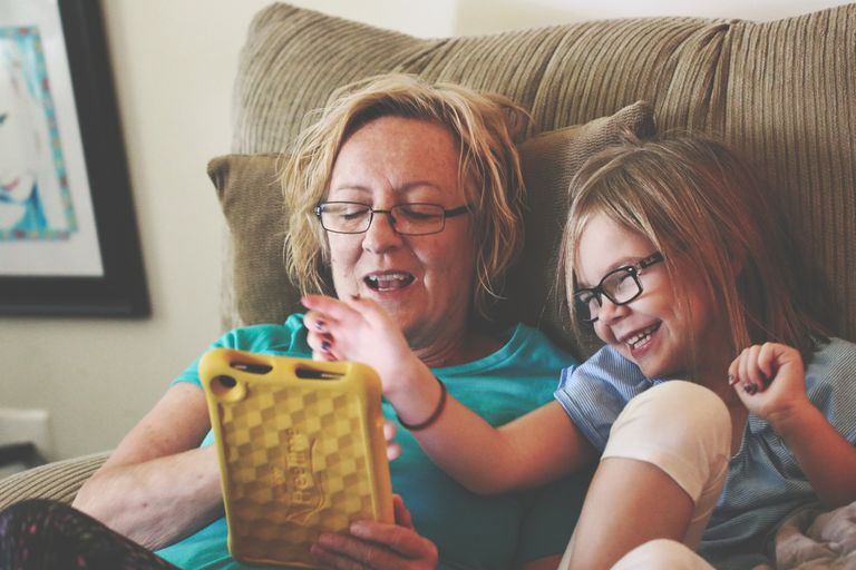 Mother and children looking at a tablet together while sitting on the couch.