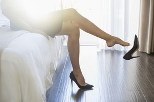 Businesswoman kicking off her shoes in hotel room