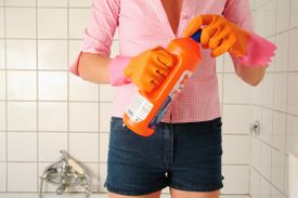 woman's midsection holding detergent bottle