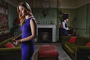 Man and woman in livingroom, woman using phone