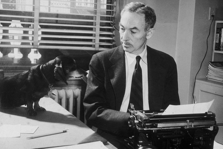 E.B. White sitting at a typewriter looking at a dachshund on the desk next to him