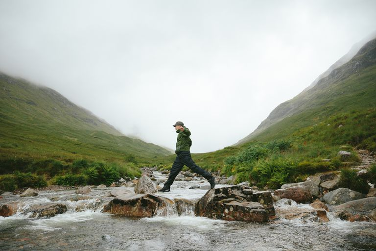 Hiker crossing river in Mountain Valley, Glencoe, Scotland