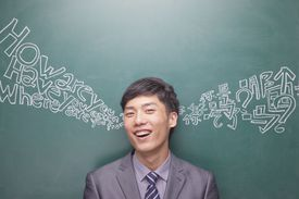 man in front of board with english and chinese characters