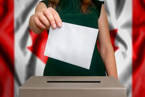 woman casting vote with Canadian flag in background