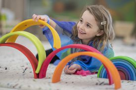 Elementary school girl building a rainbow structure