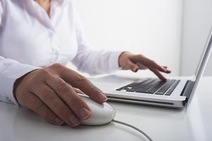 female using a laptop and a mouse