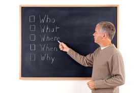 A teacher points out who, what, where, when, and why on a chalkboard