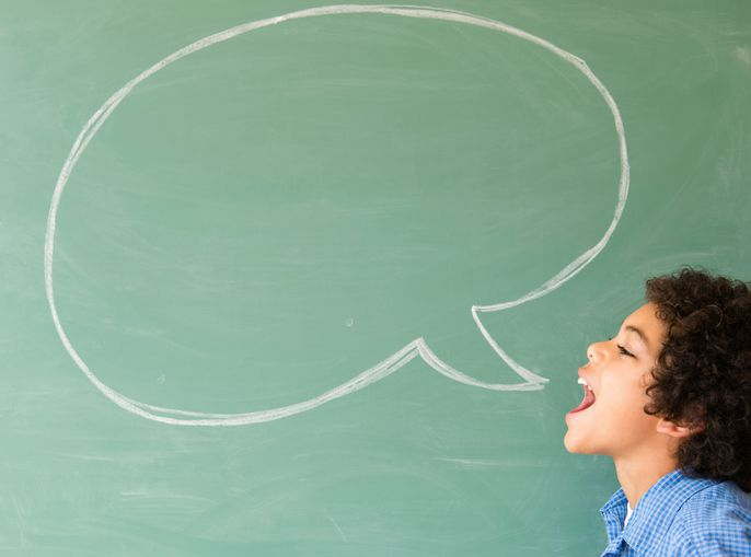 boy shouting into speech bubble on chalkboard